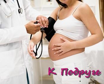 Доктор измеряет давление у беременной женщины