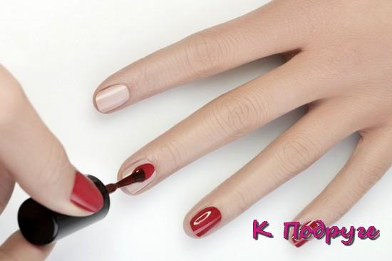 Девушка красит ногти красным лаком