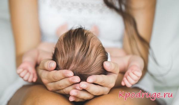 Грудной ребенок лежит на коленях у матери